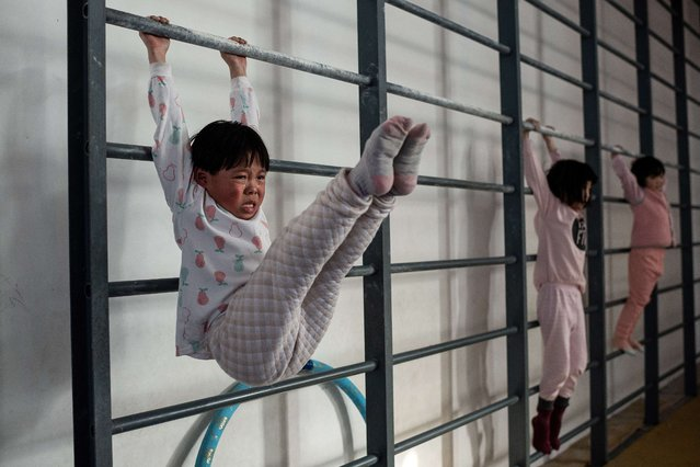 In this picture taken on January 11, 2021, young gymnasts train at the Li Xiaoshuang Gymnastics School in Xiantao, Hubei province. (Photo by Nicolas Asfouri/AFP Photo)