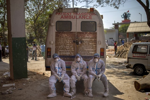 Exhausted workers, who bring dead bodies for cremation, sit on the rear step of an ambulance inside a crematorium, in New Delhi, India, Saturday, April 24, 2021. Delhi has been cremating so many bodies of coronavirus victims that authorities are getting requests to start cutting down trees in city parks, as a second record surge has brought India's tattered healthcare system to its knees. (Photo by Altaf Qadri/AP Photo)