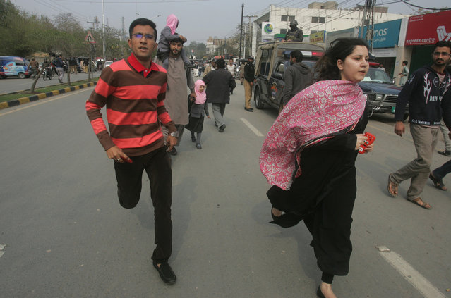 People run following a bombing in Lahore, Pakistan, Tuesday, February 17, 2015. An apparent suicide bombing killed many people outside a police complex in eastern Pakistan on Tuesday, officials said, in a rare attack on the relatively peaceful city of Lahore. (Photo by K. M. Chaudary/AP Photo)