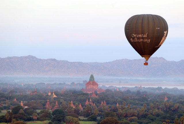 A hot air balloon flies over the Myanmar's ancient temples just before sunrise in old Bagan, Nyaung U district, central Myanmar, Thursday, October 31, 2019. (Photo by Aung Shine Oo/AP Photo)