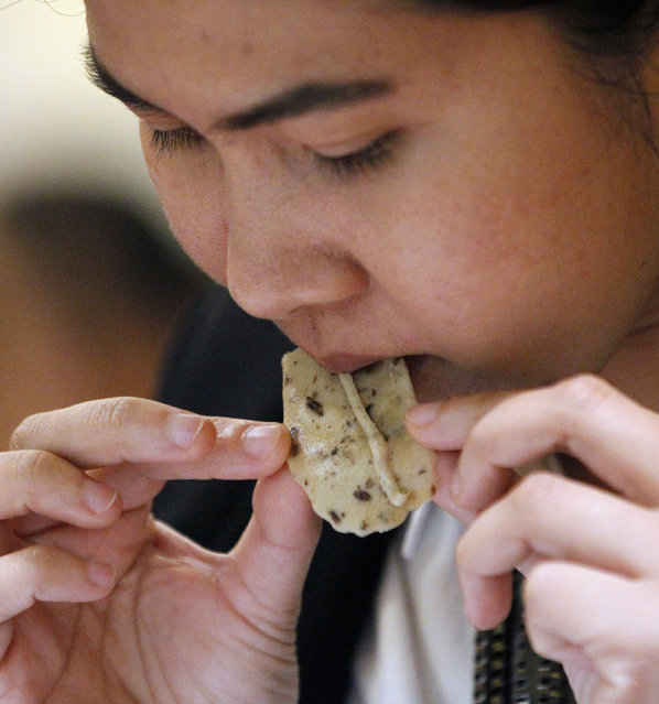 In this Thursday, February 19, 2015 photo, a participant tries an hors d'oeuvres made with insects at a seminar at Le Cordon Bleu's cooking school in Bangkok. (Photo by Sakchai Lalit/AP Photo)