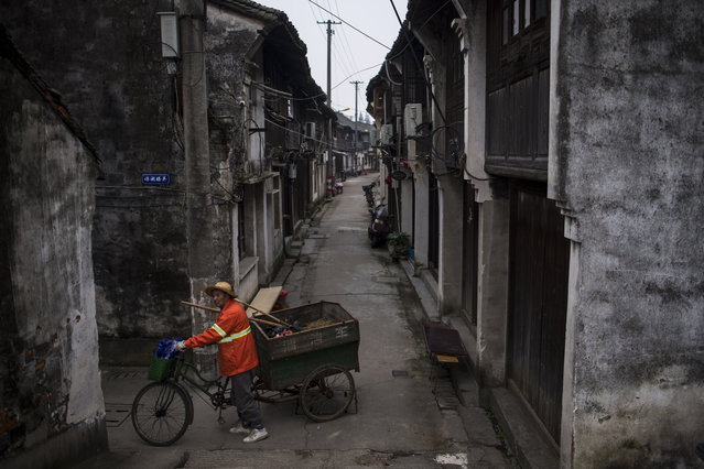 A street cleaner pushes his tricycle through the alleys of Wuzhen Township of Tongxiang City, in east China's Zhejiang  province on November 25, 2016. (Photo by Johannes Eisele/AFP Photo)