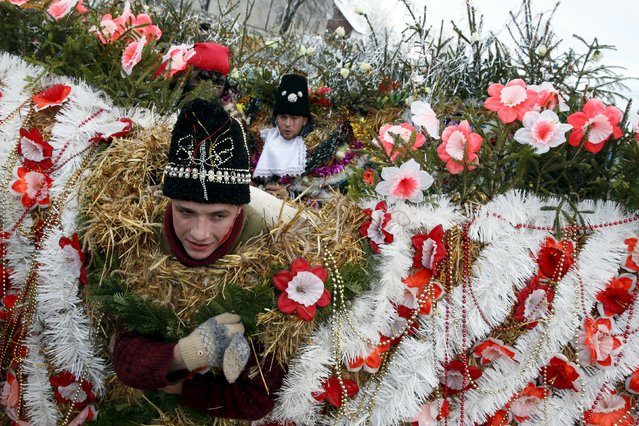Local residents dressed in costumes perform during celebrations for the Malanka holiday in the village of Krasnoilsk in the Chernivtsi region of Ukraine, January 14, 2016. The Malanka traditional holiday is more popular in the western regions of the country and is also known as the Old New Year celebrated on January 13 and 14 - St. Basil's and St. Melania's Day, according to the old Julian calendar. During the celebrations, youngsters and adults wear traditional carnival costumes and masks, and visit local houses while singing carols, playing pranks or performing short plays. (Photo by Valentyn Ogirenko/Reuters)