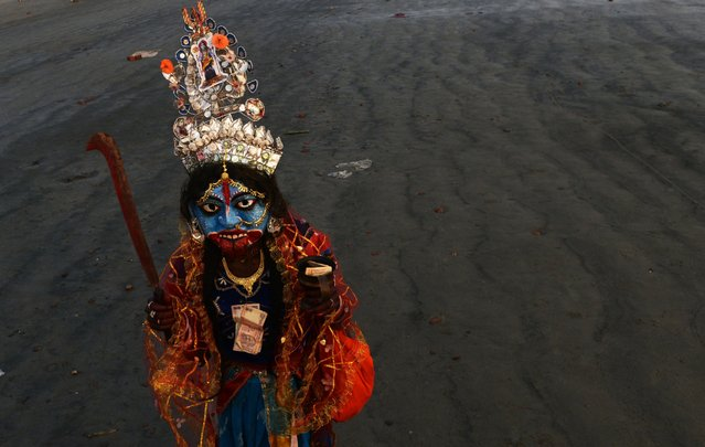 A Hindu devotee, dressed as the Hindu goddess Kali, begs for alms at Gangasagar Island, India, January 12, 2016. (Photo by Dibyangshu Sarkar/AFP Photo)