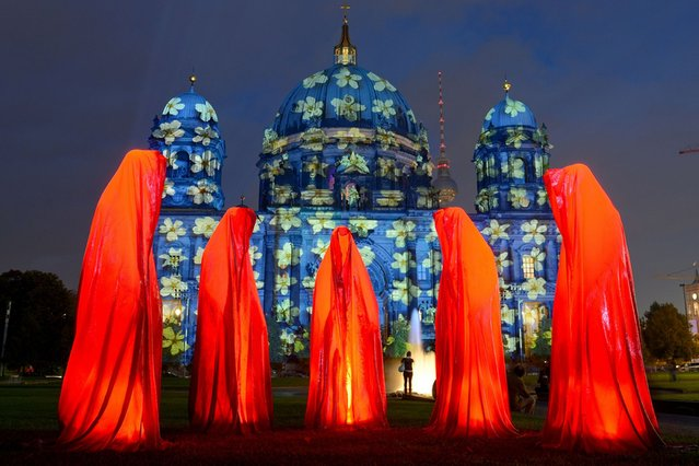 "The installation ""Keeper of Time"" is seen in front of enlightened Berlin Cathedral on the first day of Festival of Lights, on Oktober 9, 2013. (Photo by Britta Pedersen/AFP Photo)"