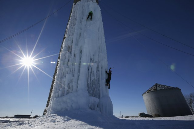 An climber ascends a silo covered in ice in Cedar Falls, Iowa, United States, January 17, 2016. (Photo by Jim Young/Reuters)