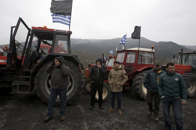 Farmers stand next to tractors during a demonstration of Greek farmers against planned pension reforms, next to the main motorway linking Athens to the north of the country, in Tempi, near the city of Larissa in central Greece, January 20, 2015. (Photo by Alexandros Avramidis/Reuters)