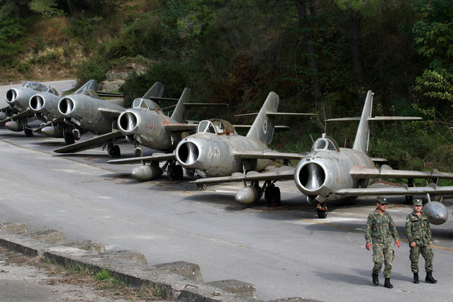 Albanian Air Force members walk near MiG-15 jet fighters in Kucova Air Base in Kucova, Albania on October 3, 2018. (Photo by Florion Goga/Reuters)