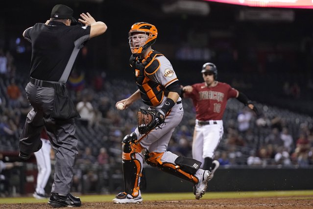 Umpire Nick Mahrley, left, calls a foul ball as San Francisco Giants catcher Buster Posey, middle, questions the call as Arizona Diamondbacks' Tim Locastro, right, runs toward home plate during the ninth inning of a baseball game Wednesday, May 26, 2021, in Phoenix. The Giants defeated the Diamondbacks 5-4. (Photo by Ross D. Franklin/AP Photo)