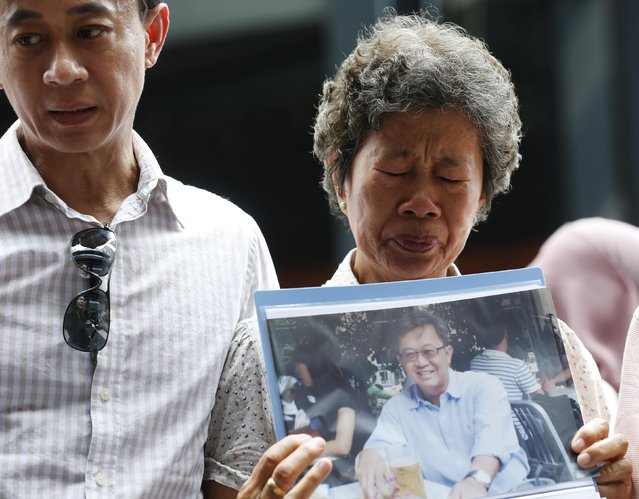 Madam Wong and her son Daniel Tan, hold a picture of her son Tan Chong Ling who was aboard missing Malaysia Airlines flight MH370, on the one year anniversary of its disappearance at a remembrance event, in Kuala Lumpur, March 8, 2015. Malaysia's Prime Minister Najib Razak said on Sunday Malaysia remains committed to the search for the missing MH370 jetliner a year after it vanished without trace and he is hopeful it will be found. REUTERS/Olivia Harris (MALAYSIA - Tags: TRANSPORT DISASTER ANNIVERSARY)