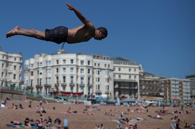 A man dives into the sea as people enjoy the hot weather on Brighton beach, in Brighton, Britain, June 1, 2021. (Photo by Hannah McKay/Reuters)