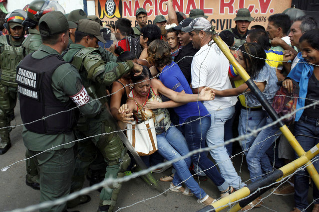 People clash with Venezuelan National Guards as they try to cross the border to Colombia over the Francisco de Paula Santander international bridge in Urena, Venezuela December 18, 2016. (Photo by Carlos Eduardo Ramirez/Reuters)