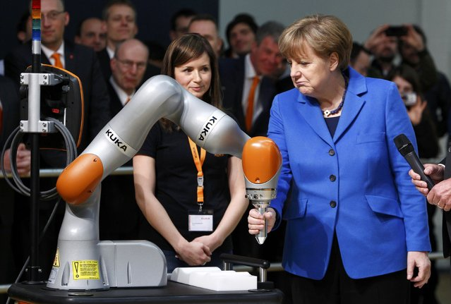 German Chancellor Angela Merkel (R) controls a robot during her visit at the robotic systems manufacture KUKA in Augsburg March 13, 2015. (Photo by Michaela Rehle/Reuters)