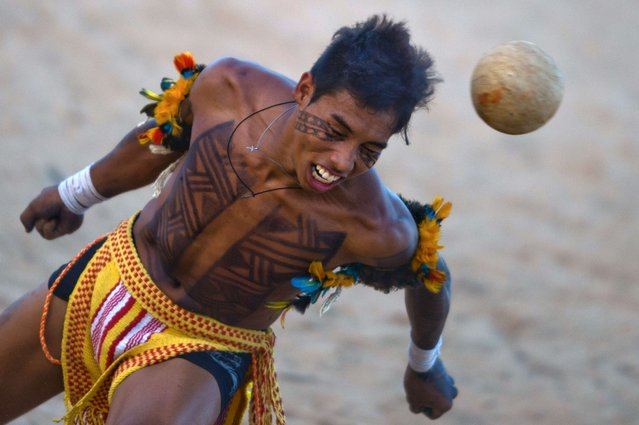 Brazilian natives of the Pareci tribe play head football with a hand-made ball for a demonstration, during the first day of the International Games of Indigenous Peoples, in Cuiaba, state of Mato Grosso, on November 10, 2013. 1500 natives from 49 Brazilian ethnic groups and from another 17 countries are gathering in Cuiaba until November 16 to compete in some 30 athletic disciplines, many of their own. (Photo by Christophe Simon/AFP Photo)