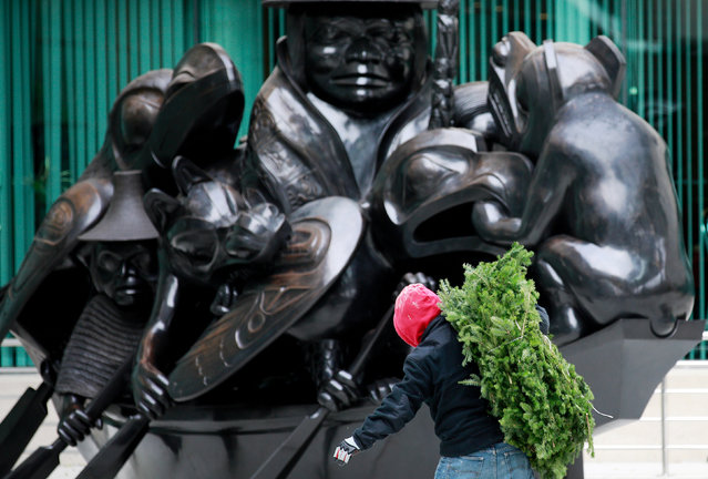 """A worker carries garlands to be used for holiday decorations past the """"Spirit of Haida Gwaii"""" sculpture by Canadian artist Bill Reid at the Canadian Embassy in Washington, DC, U.S. November 23, 2018. (Photo by Jim Young/Reuters)"""