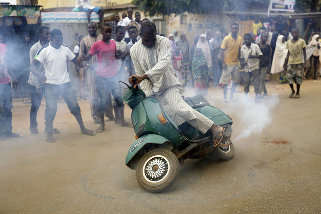Nigerians  celebrate the anticipated victory of Presidential candidate Muhammadu Buhari  by doing a burnout on a scooter in Kaduna,  Nigeria Tuesday, March 31, 2015. (Photo by Jerome Delay/AP Photo)