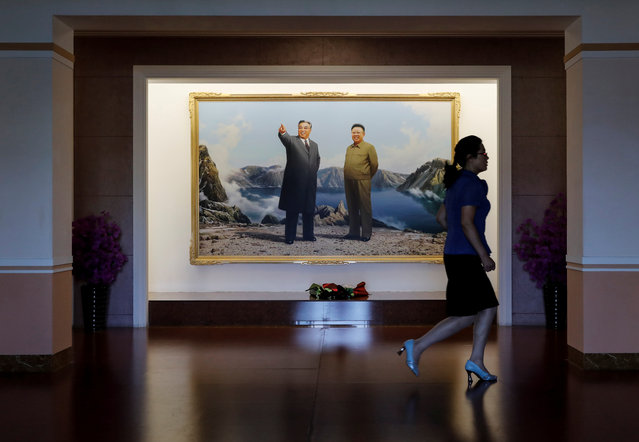 A guide walks past an image of late North Korean leaders Kim Il Sung and Kim Jong Il at a teachers' training college during a government organised visit for foreign reporters in Pyongyang, North Korea, September 7, 2018. (Photo by Danish Siddiqui/Reuters)