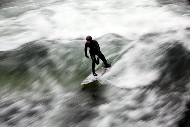 A surfer catches a wave on a freezing water of the Eisbach in Munich's famous English garden, Germany January 5, 2017. (Photo by Michael Dalder/Reuters)