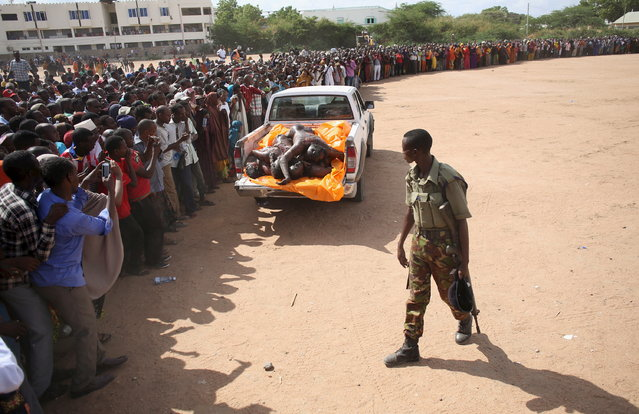 A crowd looks at bodies of suspected Garissa University College attackers in a school compound in Garissa April 4, 2015. The death toll in an assault by Somali militants on Garissa University College is likely to climb above 147, a government source and media said, as anger grew among local residents over what they say as a government failure to prevent bloodshed. (Photo by Goran Tomasevic/Reuters)