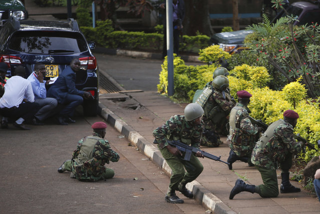 """Kenyan armed forces and civilian people take cover after an attack on a hotel, in Nairobi, Kenya, Tuesday, January 15, 2019.  Extremists launched a deadly attack on a luxury hotel in Kenya's capital Tuesday, sending people fleeing in panic as explosions and heavy gunfire reverberated through the complex. A police officer said he saw bodies, """"but there was no time to count the dead"""". (Photo by Brian Inganga/AP Photo)"""