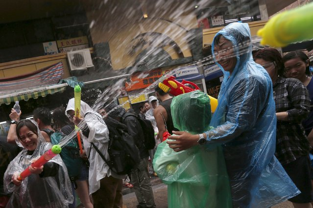 Revellers take part in a water fight during Songkran Festival celebrations at Kowloon City district, known as Little Thailand as there is large number of restaurants and shops run by Thais, in Hong Kong April 12, 2015. (Photo by Tyrone Siu/Reuters)