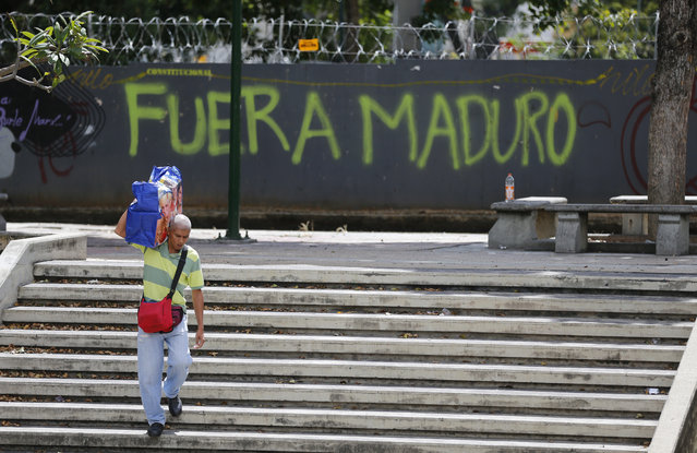"""A man walks past graffiti on the wall of a vacant lot that reads in Spanish: """"Get out Maduro"""", referring to President Nicolas Maduro in Caracas, Venezuela, Thursday, January 24, 2019. Venezuelans headed into uncharted political waters Thursday, with the young leader of a newly united and combative opposition claiming to hold the presidency and Maduro digging in for a fight with the Trump administration. (Photo by Fernando Llano/AP Photo)"""