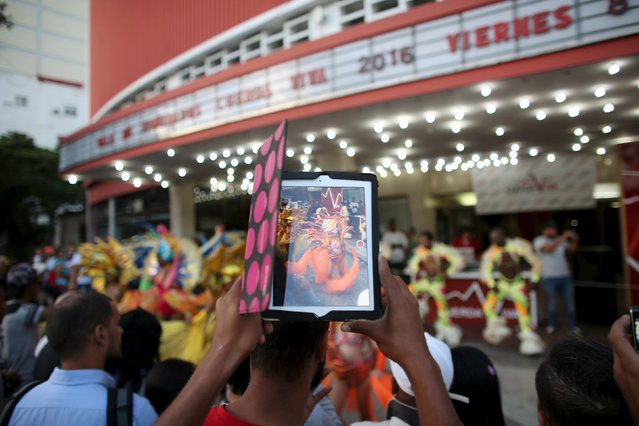 """A man records with a tablet dancers performing outside a cinema where the """"Cuerda Viva"""" (Live Strings) alternative music festival is taking place, in Havana, February 26, 2016. (Photo by Alexandre Meneghini/Reuters)"""
