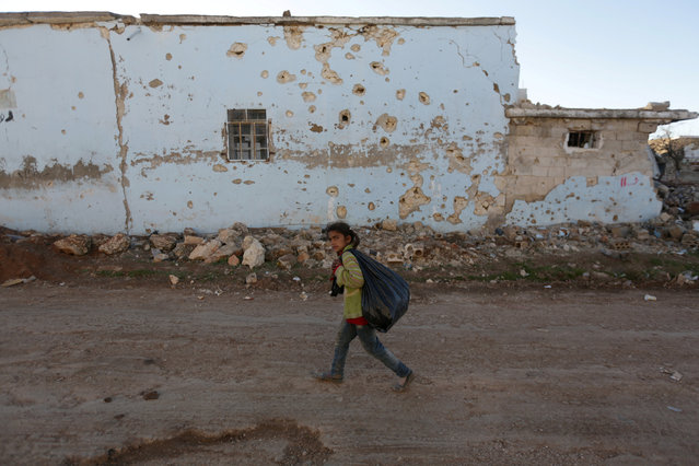 A girl walks near a riddled building in al-Rai town, northern Aleppo countryside, Syria January 13, 2017. (Photo by Khalil Ashawi/Reuters)