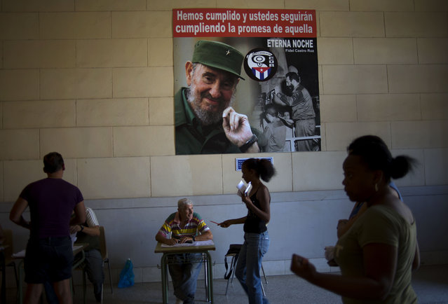 Under a picture of Cuba's leader Fidel Castro, a voter presents his identification papers before voting at a polling station in Havana, Cuba, Sunday, April 19, 2015. Cuba held its first local elections since a historic thaw in relations with the United States with an unusual wrinkle in the single-party system: two of the 27,000 candidates openly oppose the government. (Photo by Ramon Espinosa/AP Photo)