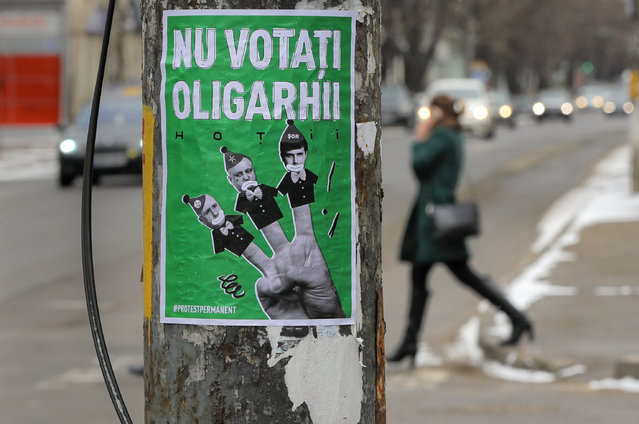"""A poster depicting, from left, Moldova's Prime Minister Pavel Filip, President Igor Dodon and Israeli born Modovan businessman and politician Ilan Shor, which reads """"Don't Vote for the Oligarchs"""" is placed on a light pole in Chisinau, Moldova, Saturday, February 23, 2019, a day before the country holds parliamentary elections. More than three million Moldovans will vote in a parliamentary elections Sunday in this former Soviet republic wedged between Romania and Ukraine choosing representatives for the 101-seat legislature for a four-year term. (Photo by Vadim Ghirda/AP Photo)"""