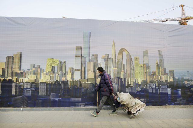 A ragpicker walks past a poster showing Beijing's central business district outside a construction site in Beijing, in this October 21, 2014 file photo. China's economy grew 7.0 percent in the first quarter of 2015, as expected but still its slowest rate in six years, reinforcing bets that policymakers will take more steps to bolster growth. (Photo by Jason Lee/Reuters)