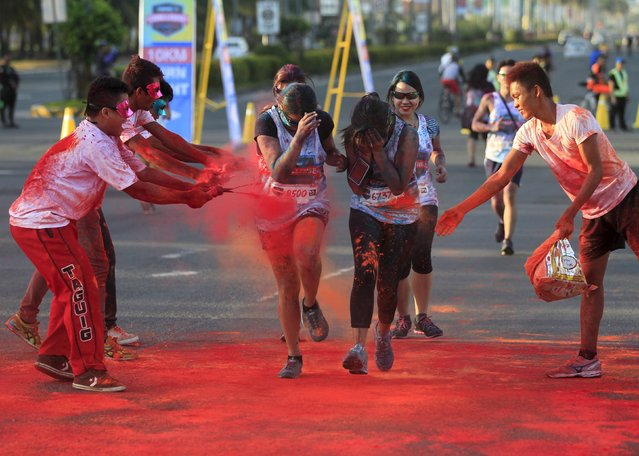 Joggers run through coloured powder thrown by race marshalls during the Manila Color Challenge in Pasay city, metro Manila April 19, 2015. Hundreds of runners joined the fun run on Sunday which aims to promote a healthier lifestyle through running. (Photo by Romeo Ranoco/Reuters)