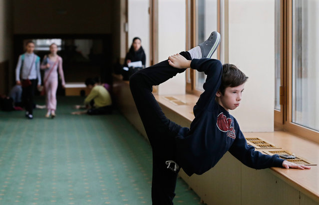 A student warms up in the hallway during the break at Moscow State Academy of Choreography in Moscow, Russia 03 March 2016. Moscow State Academy of Choreography is the oldest institution in Moscow which teaches Ballet arts not only Russian citizens, but also representatives from more than 20 countries. (Photo by Yuri Kochetkov/EPA)