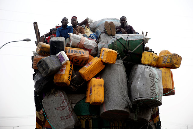 Workers sit in the back of a truck loaded with plastic containers along a road in Lagos, Nigeria December 24, 2016. (Photo by Akintunde Akinleye/Reuters)
