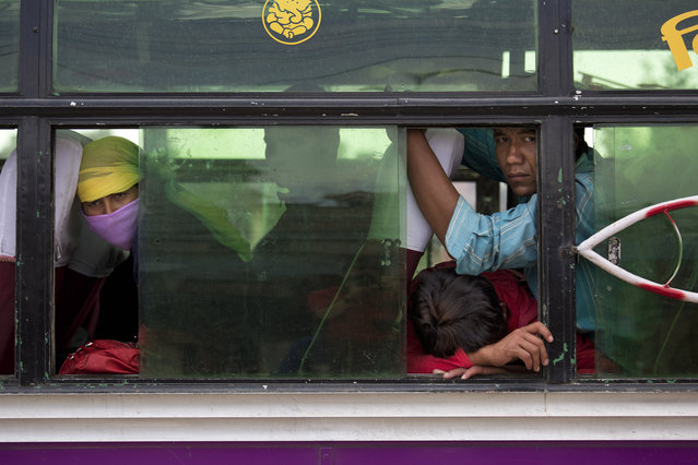 Nepalese people look out from inside a bus where they have taken shelter as it is considered safer in cars than inside houses with repeated aftershocks, in Kalanki neighbourhood of Kathmandu, Nepal, Sunday, April 26, 2015. (Photo by Bernat Armangue/AP Photo)