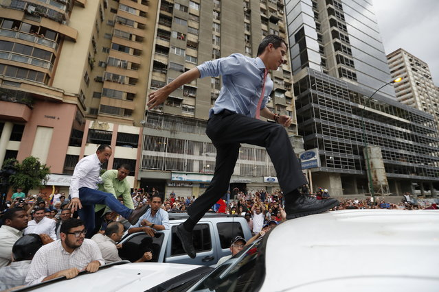 National Assembly President Juan Guaido, who declared himself interim president of Venezuela, leaps on to a vehicle to speak to supporters as he visits different points of anti-government protest in Caracas, Venezuela, Tuesday, March 12, 2019. Guaido has declared himself interim president and demands new elections, arguing that President Nicolas Maduro's re-election last year was invalid. (Photo by Eduardo Verdugo/AP Photo)