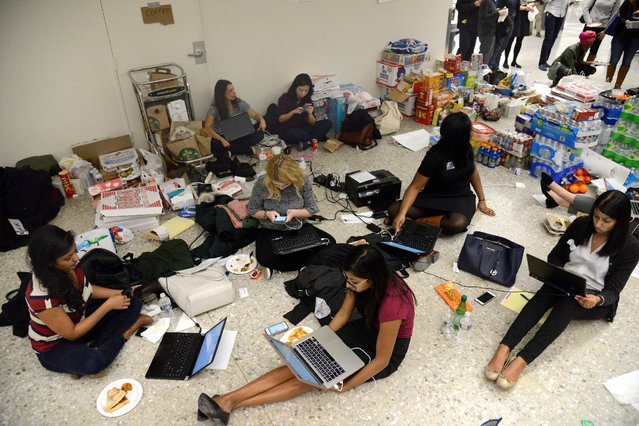 Lawyers and legal assistants network and use social media in the baggage claim area, amid supplies of pizza, water and other food, at Dulles International Airport, aiding passengers who have arrived and encounter problems because of Donald Trump's travel ban to the United States, in Chantilly, Virginia, in suburban Washington, U.S., January 29, 2017. (Photo by Mike Theiler/Reuters)