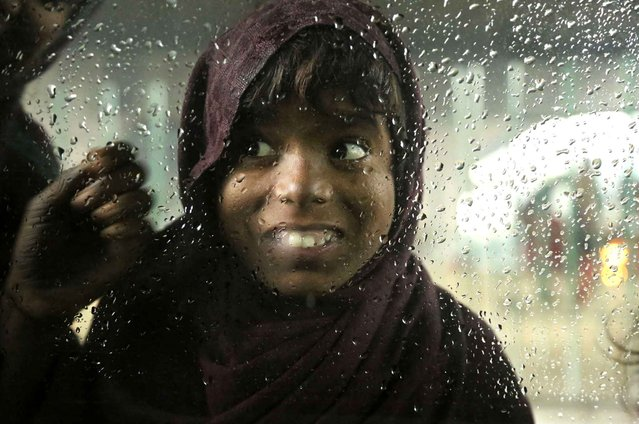 A homeless street child looks in the window of a car in Jammu, India, Friday, January 6, 2017. Some 800 million people in the country live in poverty, many of them migrating to big cities in search of a livelihood and often ending up on the streets. (Photo by Channi Anand/AP Photo)
