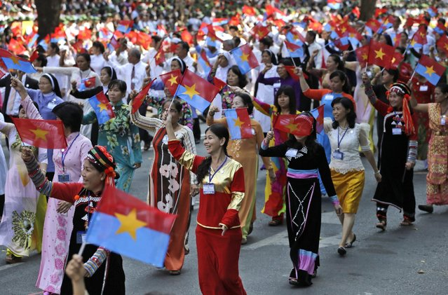 """Vietnamese women wave the National Liberation Front's and Vietnamese national flags during a parade celebrating the 40th anniversary of the end of the Vietnam War which is also remembered as the """"Fall of Saigon"""", in Ho Chi Minh City, Vietnam, Thursday, April 30, 2015. (Photo by Dita Alangkara/AP Photo)"""