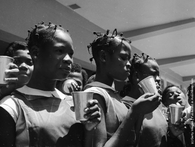June 1959:  Pupils take milk break at Queen's College in Yaba, Lagos, Nigeria, a state secondary school for girls