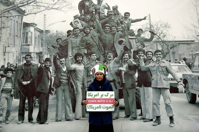 An Iranian woman holds an anti-U.S. placard as she poses in front of an undated 1979 banner photo showing people with army members celebrating the Islamic revolution, during an annual rally marking the anniversary in Azadi (Freedom) Street, in Tehran, Iran, Tuesday, February 11, 2014. Tuesday marks the 35th anniversary of the revolution that toppled the pro-U.S. Shah Mohammad Reza Pahlavi and brought Islamists to power. (Photo by Ebrahim Noroozi/Associated Press)