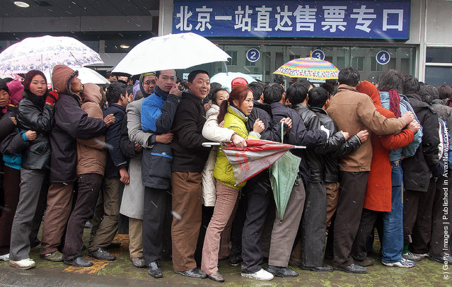 Passengers crowded in snow to buy train tickets at a railway station, China