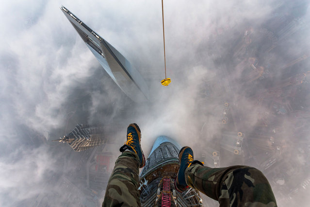 Vitaly Raskalov's feet dangle from the top of the Shanghai Tower, high above the Shanghai World Financial Centre. (Photo by Vitaly Raskalov/Caters News Agency)