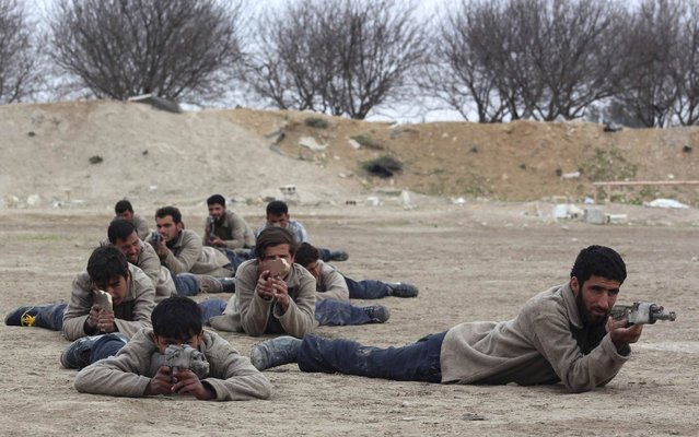 """New recruits attend a military training to be part of the """"Free Syrian Army"""" in eastern al-Ghouta, near Damascus, on February 16, 2014. (Photo by Ammar al-Bushy/Reuters)"""