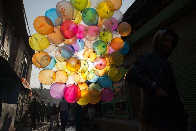 An Afghan balloon vendor walks along a street in Kabul on February 18, 2014. (Photo by Nicolas Asfouri/AFP Photo)