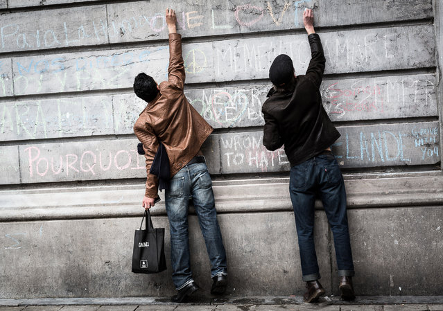 Two men write on a wall at a memorial for victims of attacks in Brussels on Wednesday, March 23, 2016. Belgian authorities were searching Wednesday for a top suspect in the country's deadliest attacks in decades, as the European Union's capital awoke under guard and with limited public transport after scores were killed and injured in bombings on the Brussels airport and a subway station. (Photo by Valentin Bianchi/AP Photo)