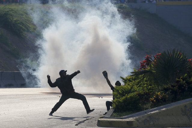 Opponents to Venezuela's President Nicolas Maduro throw stones at soldiers loyal to the president inside La Carlota airbase in Caracas, Venezuela, Tuesday, April 30, 2019. (Photo by Fernando Llano/AP Photo)