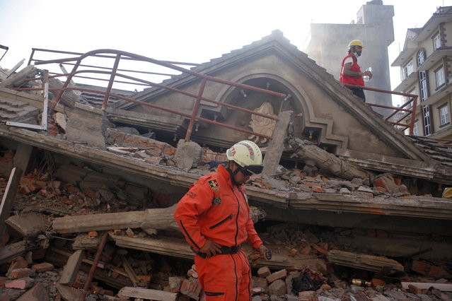 A Mexican rescue worker stands at the site of a building that collapsed in an earthquake in Kathmandu, Nepal, Tuesday, May 12, 2015. (Photo by Niranjan Shrestha/AP Photo)