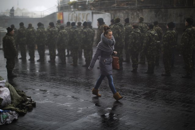 A woman passes by Ukrainian recruits receiving military instructions in Kiev's Independence Square, Ukraine, Tuesday, March 4, 2014. (Photo by Emilio Morenatti/AP Photo)