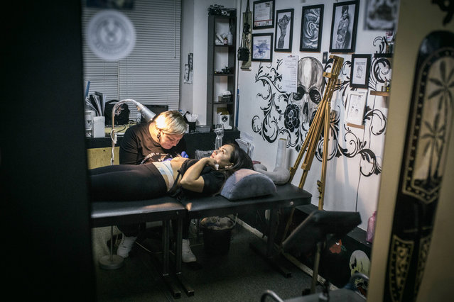 In this photo taken on Monday, December 5, 2016 tattoo artist Yevgeniya Zakhar works with a client, a victim of domestic violence, in Ufa, Russia. Yevgeniya Zakhar, a Russian tattoo artist from Ufa, a city about 1,200 kilometers (745 miles) east of Moscow, gives free tattoos to victims of domestic abuse, to cover their scars. (Photo by Vadim Braydov/AP Photo)